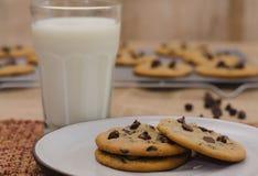 Cookies dos pedaços de chocolate na placa e no vidro do leite Foto de Stock Royalty Free