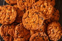 Cookies dos pedaços de chocolate no fundo rústico do preto escuro empilhado imagens de stock royalty free