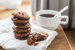 Cookies dos pedaços de chocolate no guardanapo e chá quente na tabela de madeira Fotografia de Stock Royalty Free