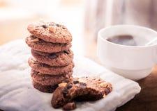 Cookies dos pedaços de chocolate no guardanapo e chá quente na tabela de madeira Imagens de Stock Royalty Free