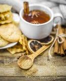 cookies e copo deliciosos do chá quente com uma vara de canela Imagem de Stock Royalty Free