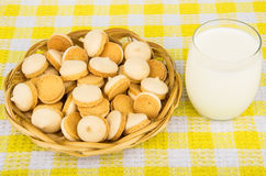 Cookies with egg glaze in wicker basket and glass milk Royalty Free Stock Image