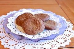 Cookies em uma placa da alfazema com os doilies brancos na tabela de madeira Imagens de Stock