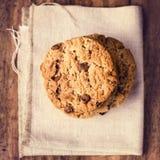 Cookies empilhadas dos pedaços de chocolate na lona de linho. Estilo country. T Fotos de Stock Royalty Free