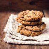 Cookies empilhadas dos pedaços de chocolate no guardanapo branco no estilo country. Fotos de Stock Royalty Free