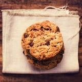 Cookies empilhadas dos pedaços de chocolate no guardanapo de linho branco em t de madeira Fotografia de Stock Royalty Free
