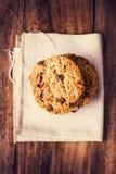 Cookies empilhadas dos pedaços de chocolate no guardanapo de linho branco em t de madeira Imagens de Stock Royalty Free