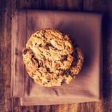 Cookies empilhadas dos pedaços de chocolate no guardanapo marrom sobre o backg de madeira Fotografia de Stock Royalty Free