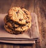 Cookies empilhadas dos pedaços de chocolate no guardanapo marrom sobre o backg de madeira Foto de Stock Royalty Free