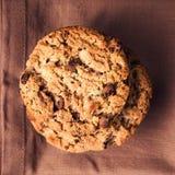 Cookies empilhadas dos pedaços de chocolate no guardanapo marrom sobre o backg de madeira Fotos de Stock