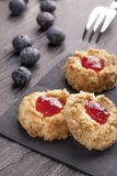 Cookies feitas do shortcake da avelã com interior do doce de morango em um guardanapo preto com mirtilos fotografia de stock royalty free