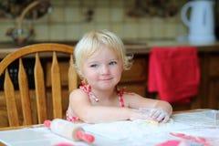 Cookies felizes do cozimento da menina na cozinha imagens de stock royalty free