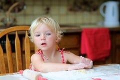 Cookies felizes do cozimento da menina na cozinha fotografia de stock