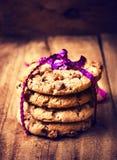 Cookies festivas dos pedaços de chocolate envolvidas com fita   em de madeira Imagem de Stock Royalty Free