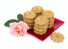 Cookies figure is a square plate with a rose. On a white background Stock Photography