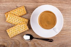 Cookies with filling, cup of coffee on saucer, spoon on table. Top view. Cookies with filling, cup of coffee espresso on saucer, spoon on wooden table. Top view royalty free stock photography