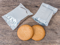 Cookies and foil package. On wood background Royalty Free Stock Photography