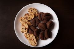 Cookies in the form of coffee beans and cereal with raisins and nuts. On a white plate stock photos