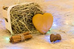 Cookies in the form of heart. Basket with hay, cinnamon and chocolate. Multicolored lights. Royalty Free Stock Photos