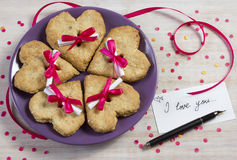 Cookies in the form of heart with a surprise. Five oatmeal cookies on a violet plate and love message Stock Photography