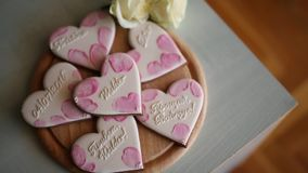 Cookies in the form of hearts. Wedding inscriptions. Pink cookie. S stock footage