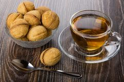 Cookies in form nut in bowl, cup of tea, teaspoon. Cookies with stuffed in form nut in bowl, cup of tea and teaspoon on dark wooden table Royalty Free Stock Photography