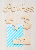 Cookies in the form of puzzles and letters on the table Royalty Free Stock Images