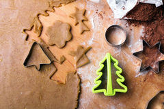 Cookies forms and gingerbread dough on wooden pastry board Stock Images
