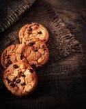 Cookies frescas dos pedaços de chocolate na tabela de madeira velha escura com lugar foto de stock