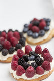 Cookies with fresh berries. Cookies with whipped cream and berries on white background Stock Images