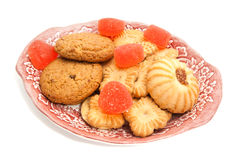 Cookies and fruit candy on glass plate. Cookies and fruit candy on a plate on white closeup Stock Photography