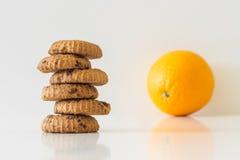 Cookies or fruit, cookies in focus, orange blurred, diet choice concept Stock Photos