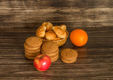 Cookies, fruits and croissants. On a wooden background Royalty Free Stock Image
