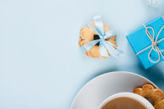 Cookies with gift and cup of coffee on blue, top view Stock Photo