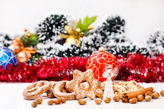 Cookies, glass angel, nuts, cinnamon sticks. On Christmas theme background stock image