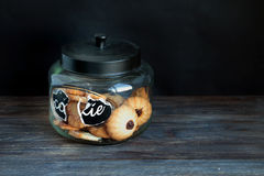 Cookies in glass jar on a wooden table. Sweet tooth concept. Cookies in glass jar on a wooden table. Special light, copy space. Sweet tooth concept Stock Images