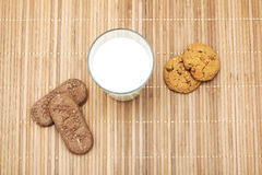 Cookies and a glass of milk on a bamboo table cloth Stock Images