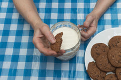 A person dunking a cookie in a glass of milk. Eating cookies , drinking a glass of milk Royalty Free Stock Images