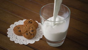 Cookies and glass of milk, on wooden table stock video footage