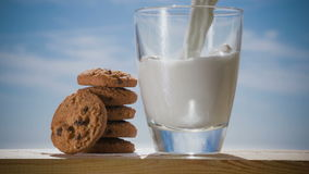 Cookies and glass of milk, on wooden table stock video