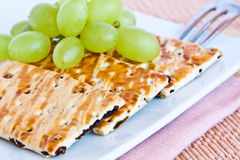 Cookies with green grapes. Cookies with raisins ane green grapes on a plate Royalty Free Stock Photography