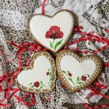 Cookies heart decorated with red poppies in vintage style on wooden background for Valentine`s Day. Present for Women`s Day or stock images