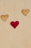 Cookies in heart shape on background. Cookies in heart shape and red felted yoys hanging over beige background place for text Royalty Free Stock Photo