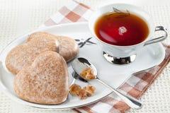 Cookies heart shape, brown sugar, spoon, black tea Royalty Free Stock Image