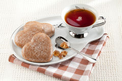 Cookies heart, sugar, spoon, black tea, saucer Royalty Free Stock Image