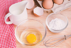 Cookies ingredients.Bowl, flour, eggs, jar of milk, eggbeater Royalty Free Stock Photography