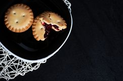 Cookies with jam on black plate on black backgroung. Up view stock photo