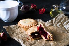Cookies with jam on brown paper on black backgroung. With white cup royalty free stock images