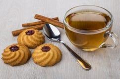 Cookies with jam, cinnamon sticks, cup of tea and teaspoon Royalty Free Stock Image