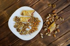 Cookies with jam, a mixture of pistachios, walnuts and almonds lie in a white plate on a wooden table made of pine boards. Farm stock images